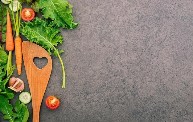 Здоровая еда и кулинария концепции деревянные лопатка и овощи на темном камне.