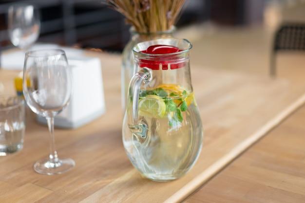 健康的な食べ物と飲み物。カフェの木製テーブルにミントとレモンのガラスマグカップの水