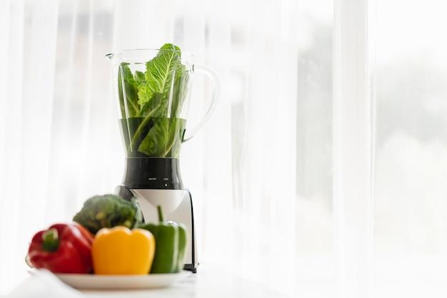 健康食品とブレンダーマシンの朝の光窓と新鮮な野菜と良い食事