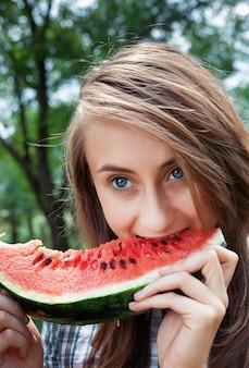 건강한 음식과 건강한 라이프 스타일 개념. 젊은 행복 한 여자는 수 박 조각을 먹고있다