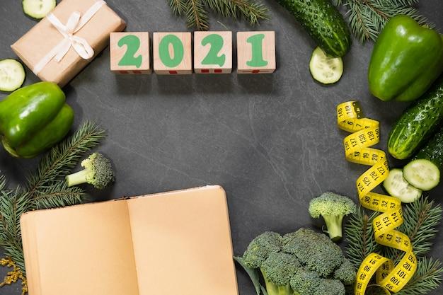 Здоровое питание и меню на рождество и новогодний стол. вид сверху овощей, измерительная лента, концепция потери веса в праздники. копирование места, список покупок