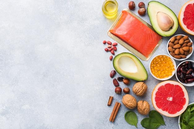 Полезные антиоксидантные продукты: рыба и авокадо, орехи и рыбий жир, грейпфрутовый шпинат и масло на сером бетонном фоне. копировать пространство