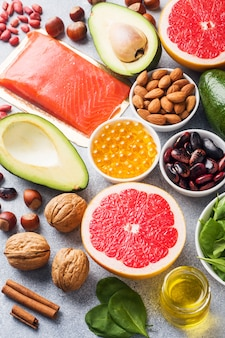 Healthy food antioxidant products: fish and avocado, nuts and fish oil, grapefruit spinach and oil on a gray concrete background.