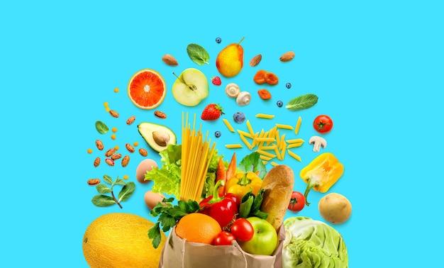 Ассортимент здоровой пищи в хозяйственной сумке и вокруг нее. овощи и фрукты, продукты на синем фоне.