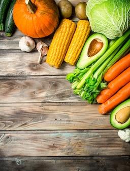 健康食品。新鮮な有機果物と野菜の品揃え。木製の背景に。