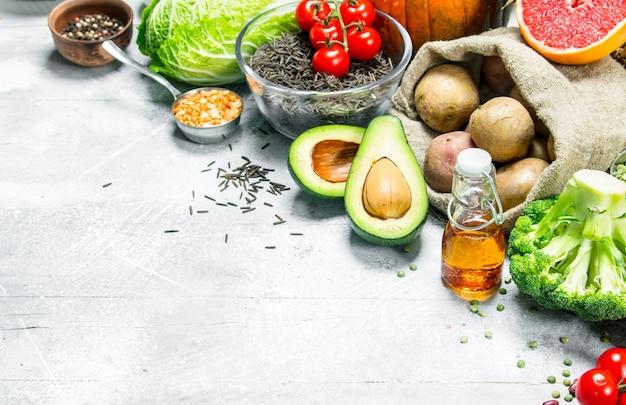 健康食品。マメ科植物と有機野菜や果物の品揃え。素朴な背景に。