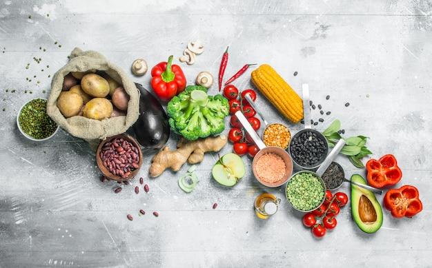 Здоровая пища. ассортимент органических овощей и фруктов с бобовыми на деревенском столе.