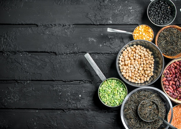 Healthy food. assotriment of legumes. on a black rustic surface.