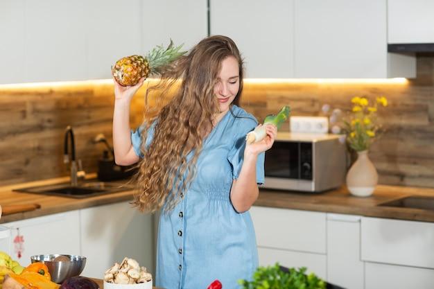 自宅で健康食品。幸せな巻き毛の女性は、モダンなキッチンでパイナップルを踊っています。ビーガンとベジタリアンのライフスタイル。健康的な食事のコンセプト。ダイエット。果物。ダイエットのコンセプトです。横型