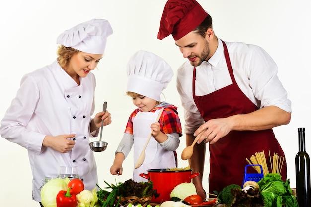 家庭での健康食品。夕食を準備するキッチンで幸せな家族。両親が料理をしている息子。