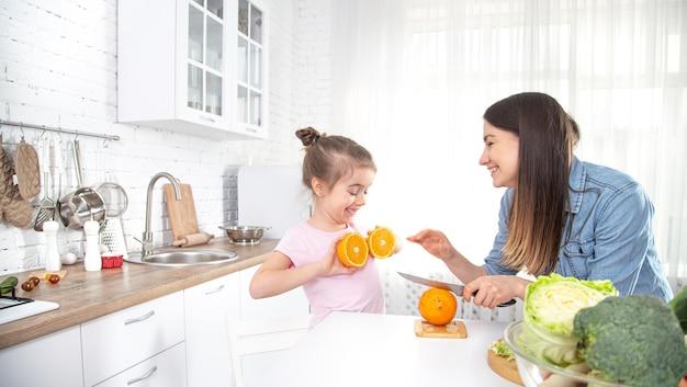 自宅で健康食品。台所で幸せな家族。母と子の娘が野菜や果物を準備しています。ビーガンフード