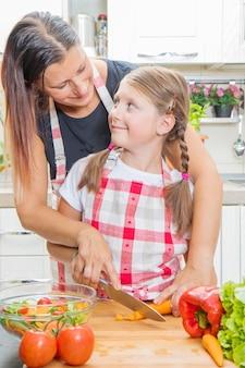 家庭での健康食品。キッチンで幸せな家族。母と子の娘が野菜を準備しています