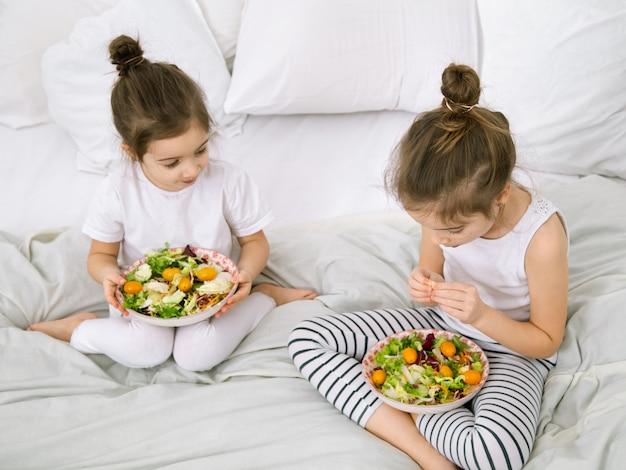 自宅で健康食品。ベッドの上の寝室で果物と野菜を食べて幸せな2人のかわいい子供。子供とティーンエイジャーのための健康食品。
