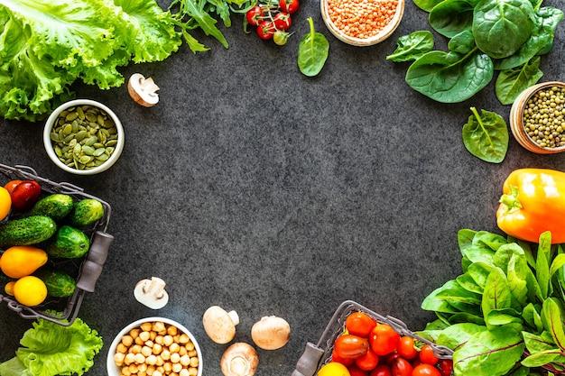 健康食品の背景。コピースペース、上面図と暗い石のテーブルの上の秋の新鮮な野菜