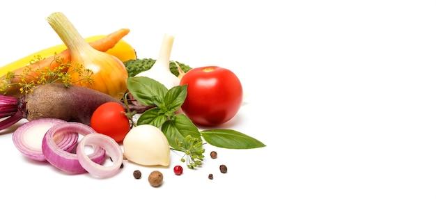健康食品の背景。バナー。テキスト、玉ねぎ、ニンニク、ビート、トマト、バジル、スパイスのためのスペースと白い背景の上の新鮮な野菜。きれいなビーガン食のコンセプト、コピースペース
