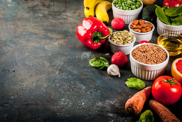 Healthy food background, trendy alkaline diet products - fruits, vegetables, cereals, nuts. oils, dark blue concrete background copy space