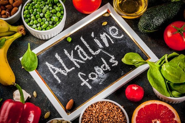 Healthy food background, trendy alkaline diet products - fruits, vegetables, cereals, nuts. oils, dark blue concrete background