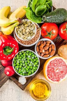 Здоровая пища фон, модные щелочные диетические продукты - фрукты, овощи, крупы, орехи. масла, светлый бетонный фон над крупным планом