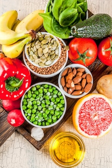 Healthy food background, trendy alkaline diet products - fruits, vegetables, cereals, nuts. oils, light concrete background  above close view