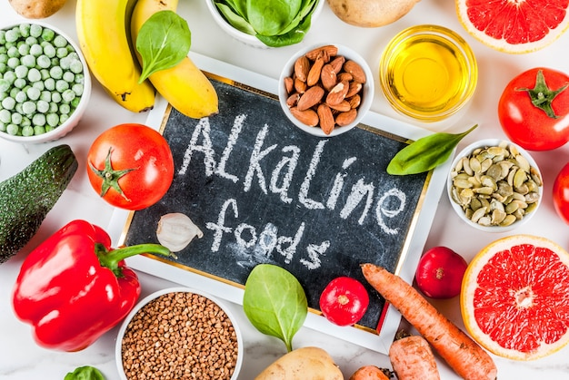 Healthy food background, trendy alkaline diet products - fruits, vegetables, cereals, nuts. oils, white marble background above