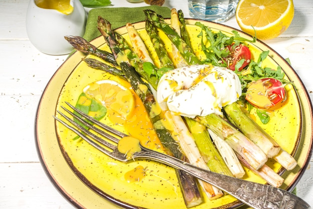 Healthy food, baked grilled asparagus, poached egg and hollandaise sauce