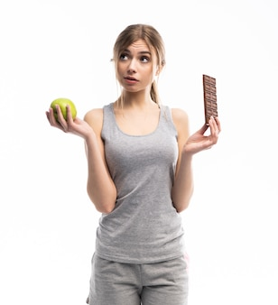 健康食品。健康食品と不健康な食品のどちらかを選択する美しい若い女性