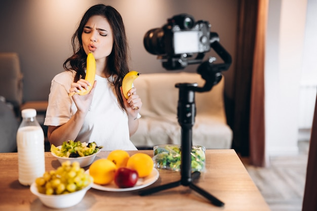 Healthy food blogger young female cooking fresh of fruits vegan salad in kitchen studio, filming tutorial on camera for video channel. female influencer shows no junk food, talks about healthy eating.