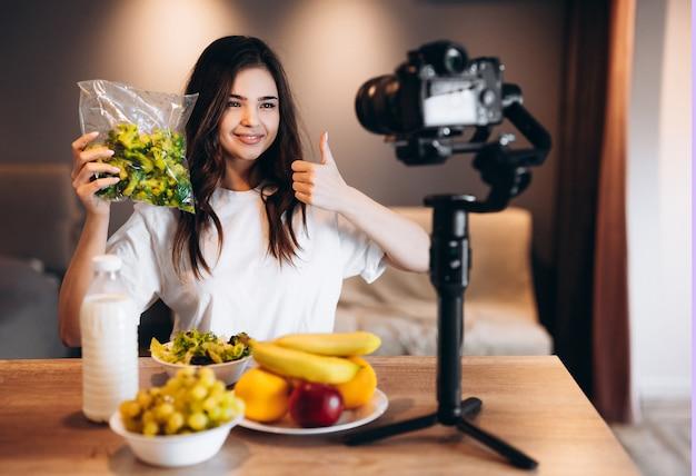 健康食品ブロガーの若い女性がキッチンスタジオでフルーツビーガンサラダを新鮮に調理し、ビデオチャンネルのカメラでチュートリアルを撮影しています。若い女性のインフルエンサーは、健康的な食事への彼女の愛を示しています。