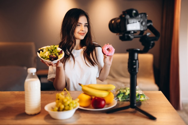Healthy food blogger young female cooking fresh vegan salad of fruits and saying no to sweets in kitchen studio