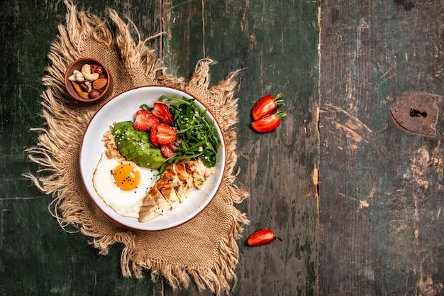 健康食品。ルッコラとイチゴのチキンサラダボウル。テキストのバナーメニューレシピ場所。上面図
