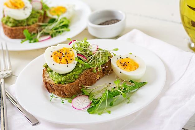 健康食品。朝ごはん。白い木製の表面に全粒粉パンとアボカドの卵サンドイッチ。