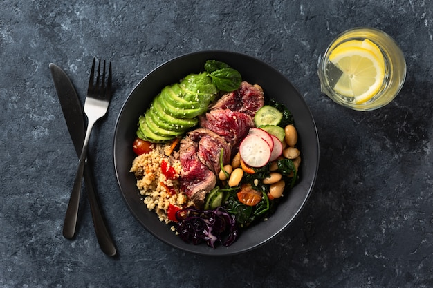 Healthy food buddha bowl with beef steak, beans, couscous, avocado and vegetables