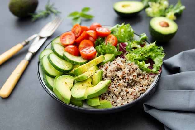 Healthy food. budha bowl with quinoa, avocado, cucumber, salad, tomatoe, olive oil.