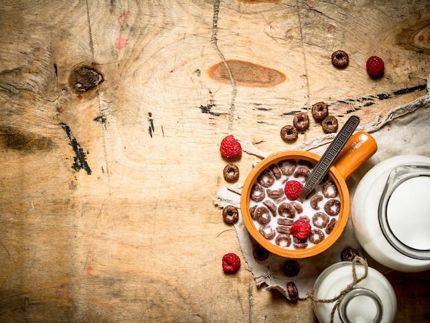 건강한 음식. 라스베리와 우유와 초콜릿 시리얼. 나무 테이블에.