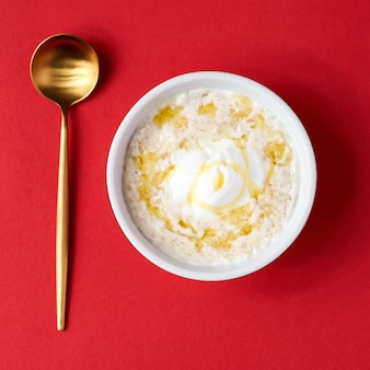 Каша здоровой еды классическая в белом шаре на красной стене, селективном фокусе. овсяная каша в сочетании с завтраком.