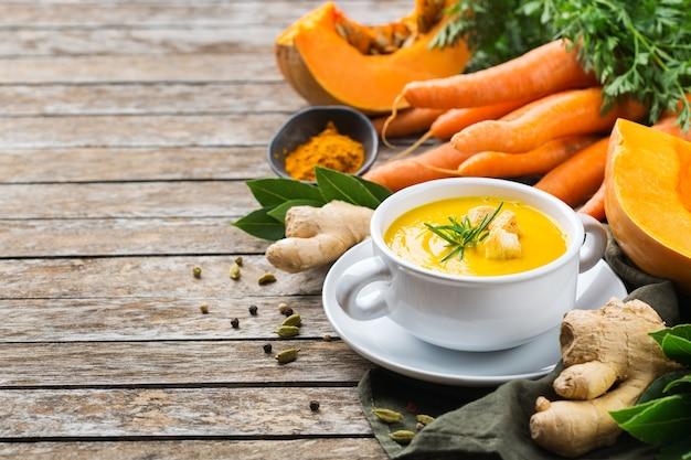 Здоровое питание, концепция чистого питания. сезонные пряные осенние овощи сливочный суп из тыквы и моркови с ингредиентами на деревенском деревянном столе. скопируйте космический фон