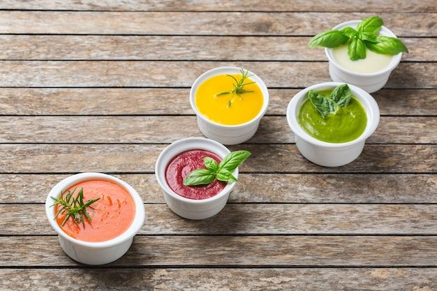 Здоровое питание, концепция чистого питания. разнообразие красочных сезонных осенних овощных сливочных супов с ингредиентами. тыква, брокколи, морковь, свекла, картофель, томатный шпинат. копировать пространство