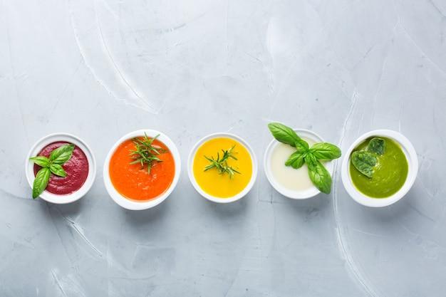 Здоровое питание, концепция чистого питания. разнообразие красочных сезонных осенних овощных сливочных супов с ингредиентами. тыква, брокколи, морковь, свекла, картофель, томатный шпинат. плоская планировка, копия пространства