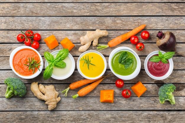 健康食品、きれいな食事のコンセプト。色とりどりの旬の秋野菜の具材入りクリーミースープ。カボチャ、ブロッコリー、ニンジン、ビートルート、ジャガイモ、トマトほうれん草。フラットレイ