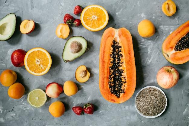Выбор здоровой пищи, чистой еды: фрукты, ягоды, семена чиа, суперпродукты на сером бетонном фоне. вид сверху, плоская планировка. фото высокого качества