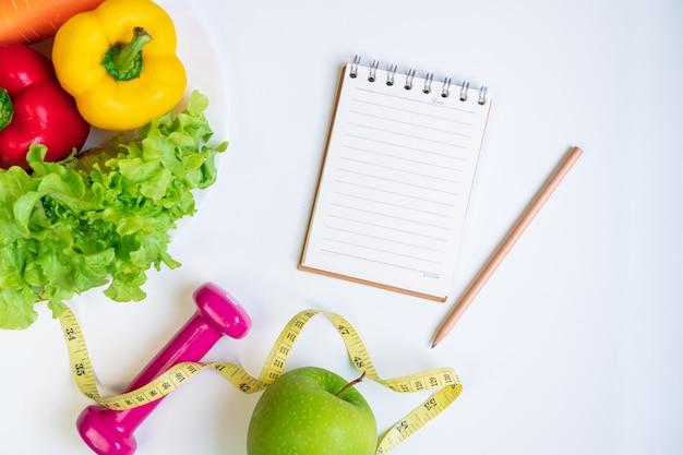 白いテーブルの背景に果物野菜ダンベルノートブックと巻尺で健康食品きれいな食事の選択
