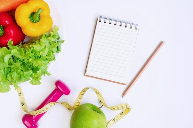 白の果物、野菜、ダンベル、ノートブックと巻尺で健康食品のきれいな食事の選択