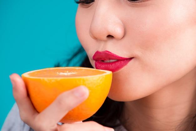 건강한 음식. 파란색 배경 위에 오렌지를 들고 있는 아름다운 핀업 아시아 소녀 dmiling의 클로즈업.