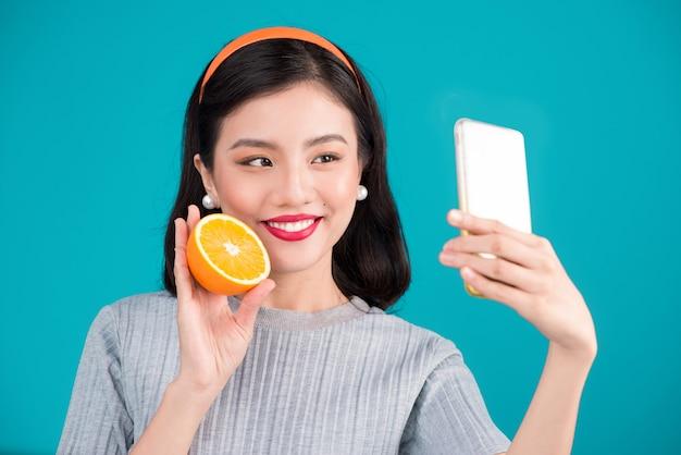 健康食品。オレンジ色を保持し、青い背景の上に自分撮り写真を撮る笑顔の素敵なピンナップアジアの女の子のクローズアップ。