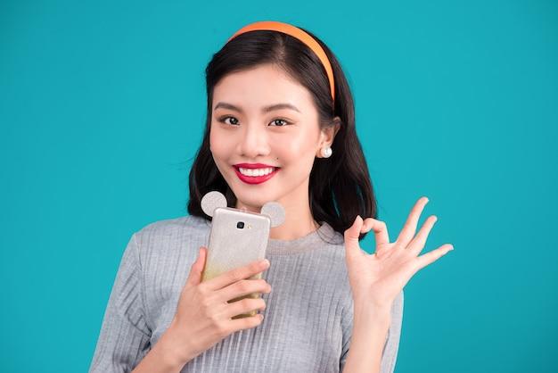 健康食品。青い背景の上にスマートフォンを保持している笑顔の素敵なピンナップアジアの女の子のクローズアップ。