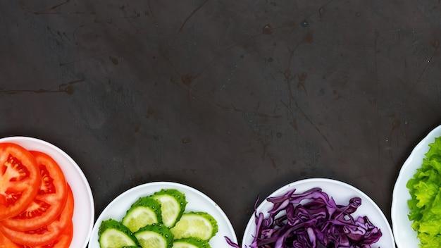 健康的な食品組成。スライスした野菜を皿に盛り付ける