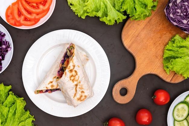 健康的な食品組成。野菜と皿にピタロールの半分にカット