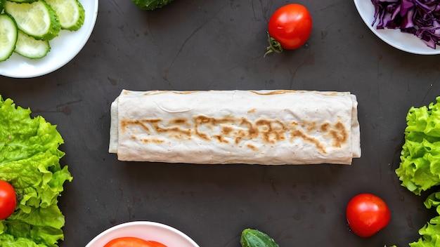 Состав здорового питания. овощи на посуде и рулет из лаваша
