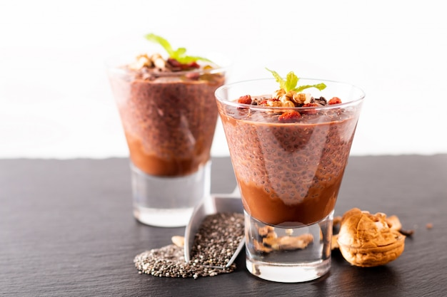 Healthy food concept chia seeds, chocolate milk pudding with goji and dried walnuts in small glass on black slate board background