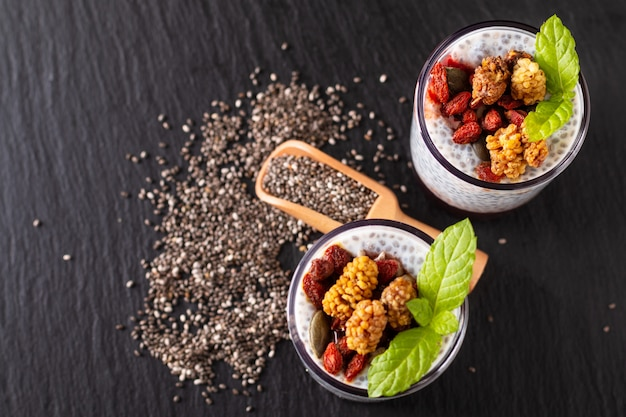 Healthy food concept chia seeds, milk pudding with goji, white mulberry and mix dried seeds in small glass on black slate board background